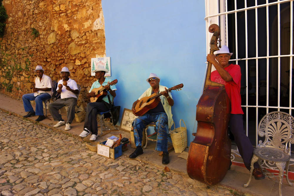 A group of Cuban men playing music on a cobbled street