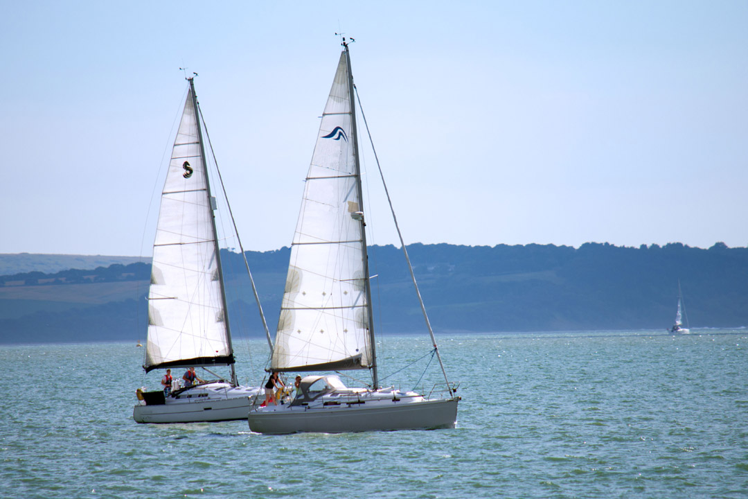 Two yachts sailing side by side with the coast in the background