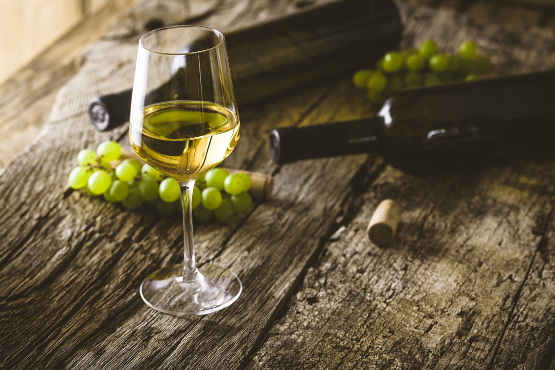 A glass of white wine with bottles and grapes in the background