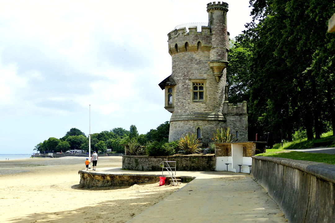 A small crenellated turret on the beach surrounded by green trees