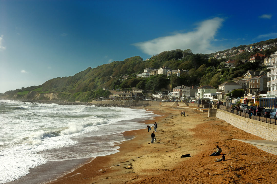 Waves roll onto a golden beach with a small town built into the cliff
