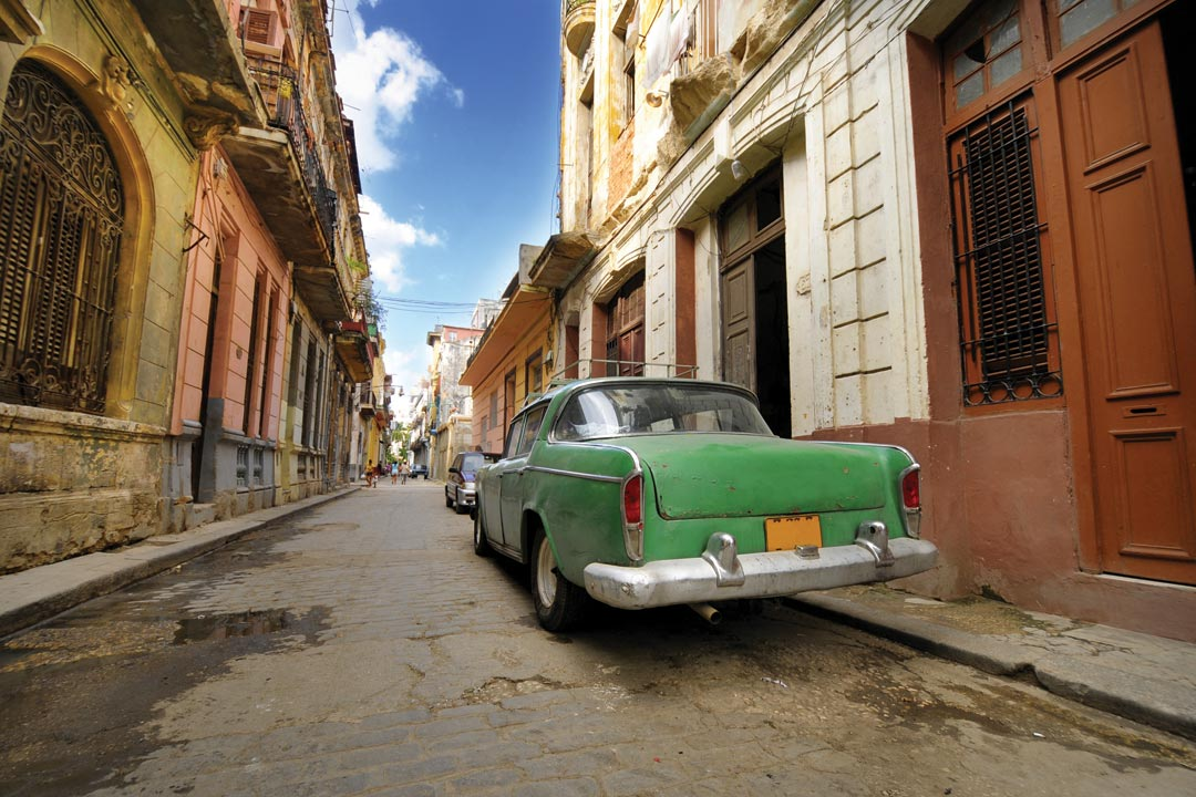 A Cuban side street of crumbling colonial buildings with vintage cars parked up.