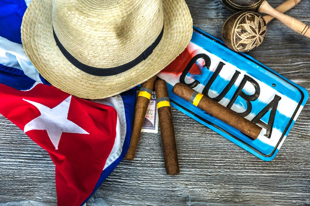 Cuban cigars, a registration plate saying 'Cuba', a pair of maraccas, a sun hat and a Cuban flag lie on a table