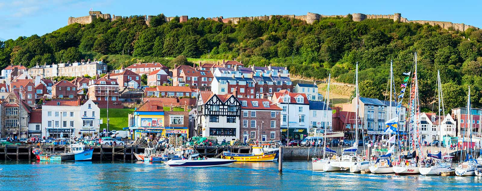 Scarborough seafront, boats are moored in the harbour, old town houses stand at the foot of the cliff which is topped by the ruins of the castle