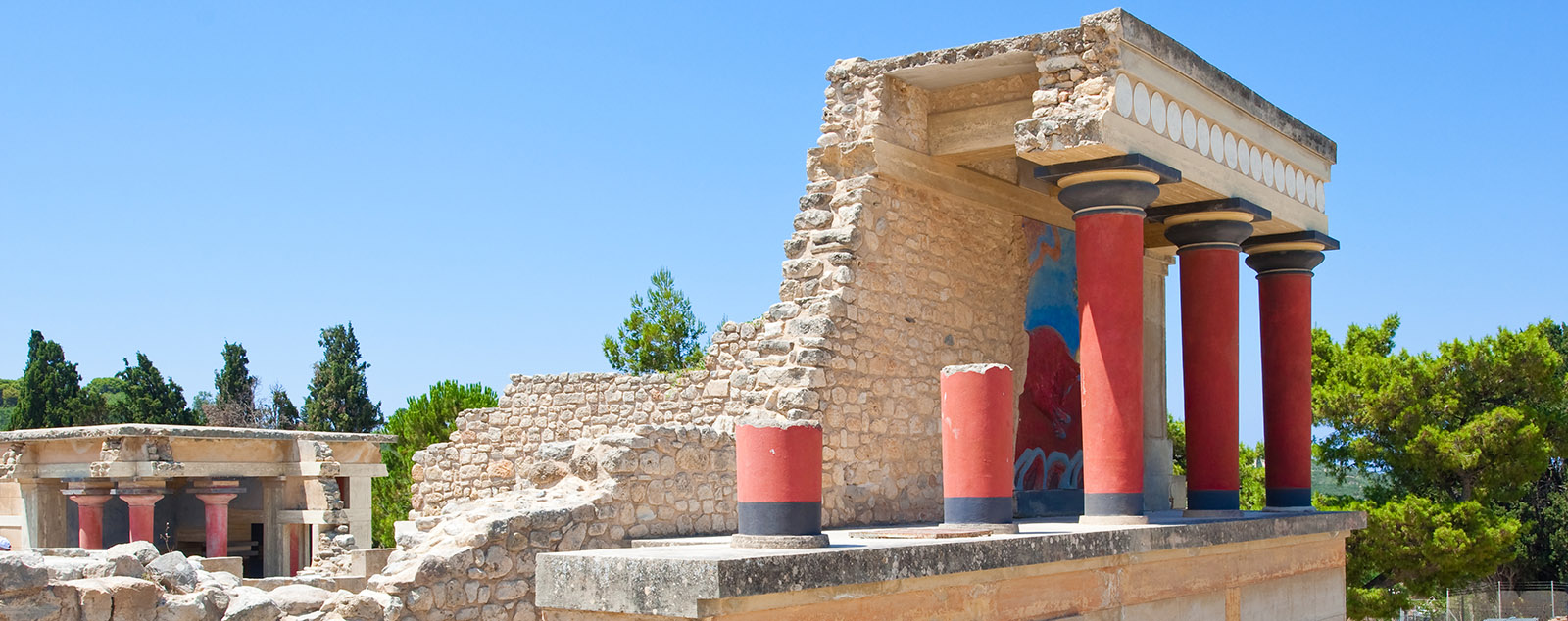 Knossos palace, red pillars prop up the ancient structure, a mural of a bull can be seen, with further ancient pillared structures in the background