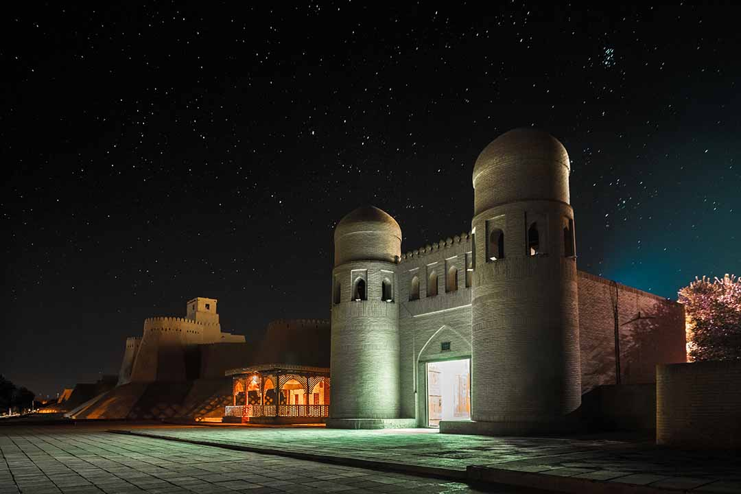 The Western gate of the walled inner town of Khiva. Domed guard towers are on either side of the gate. The wall stretches off into the distance. The sky is clear and full of stars.