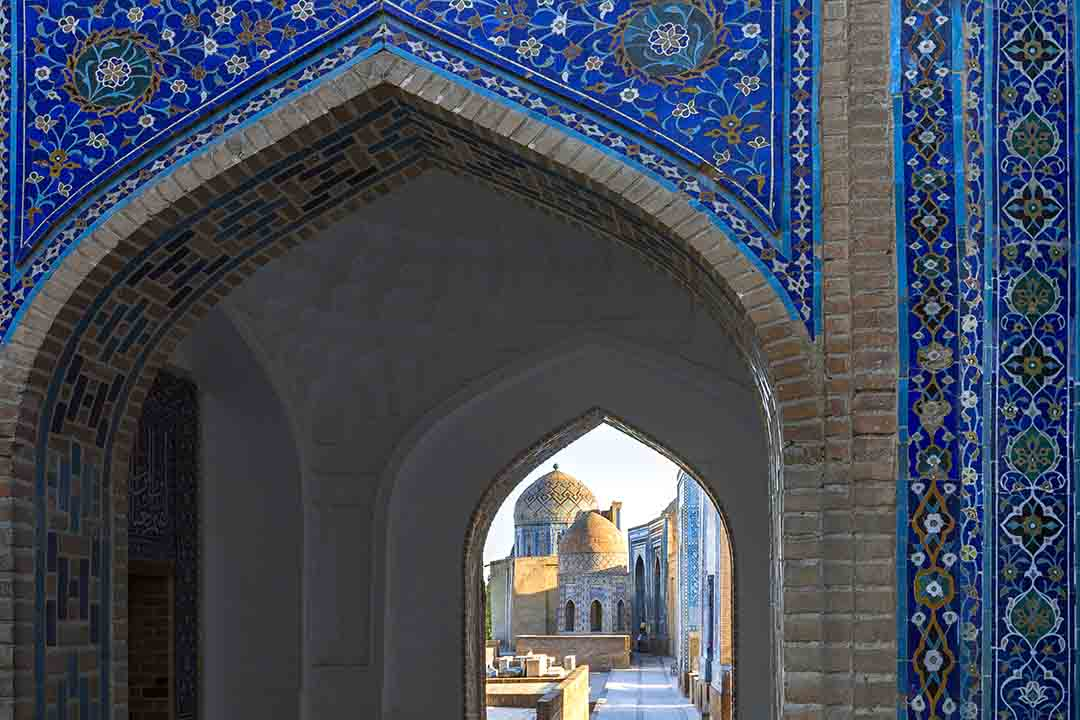 Monumental gate of the ancient necropolis of Shakhi Zinda in Samarkand. The gate is patterned with flowers and imagery.