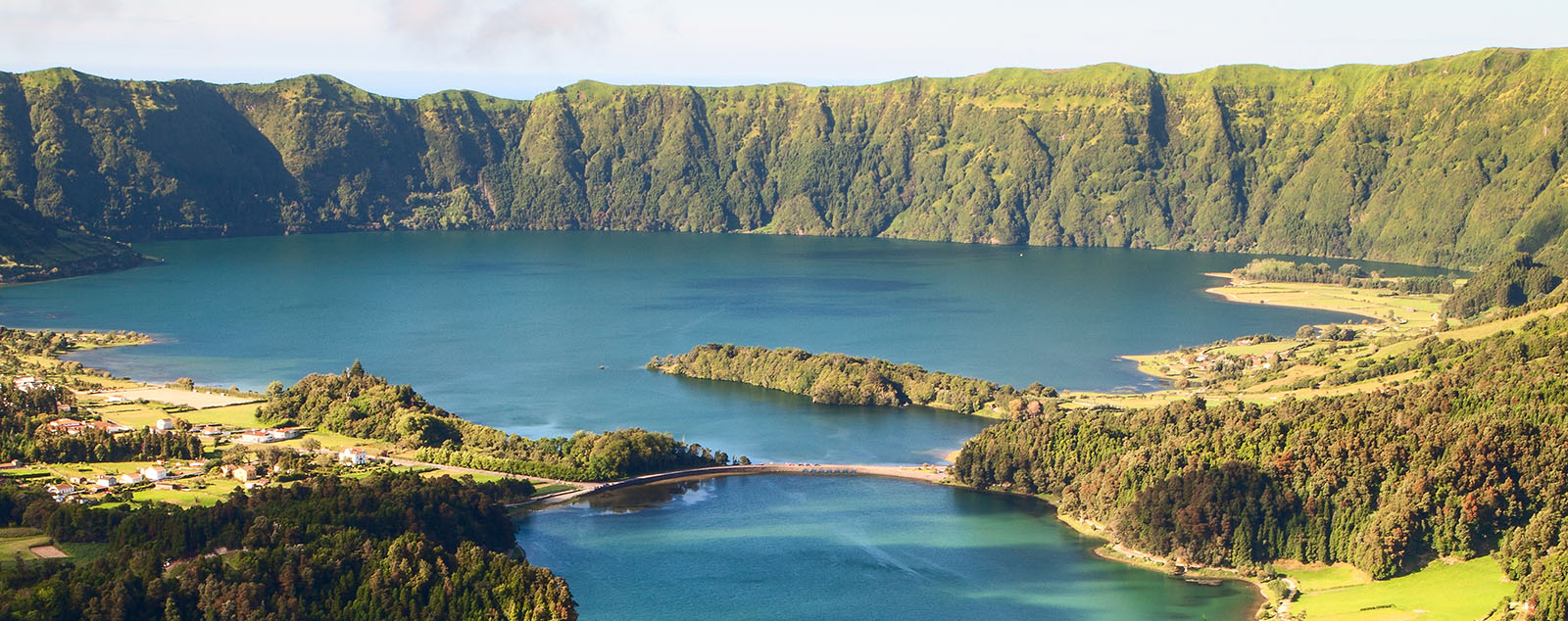 A volcanic crater lake. Huge steep cliffs lead down to the water. The landscape is dotted with dense green forest.