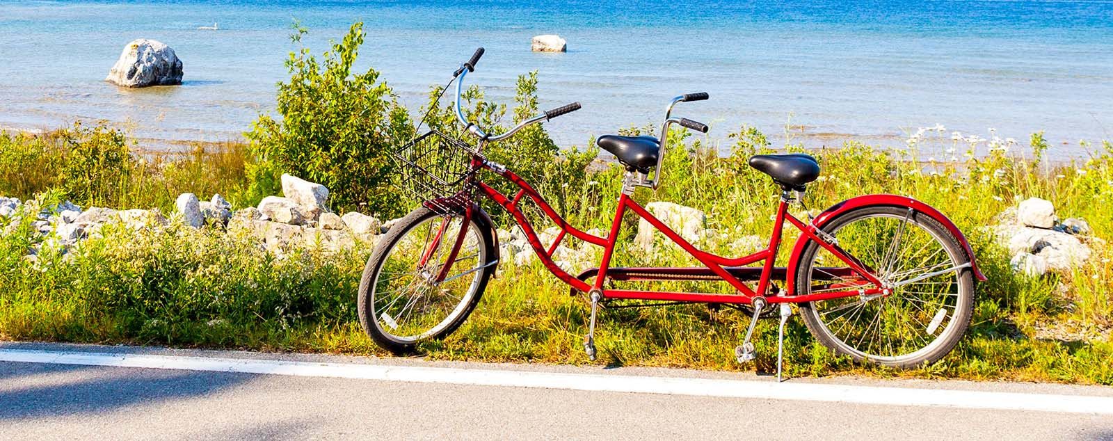 A red tandem bike parked on a beach road