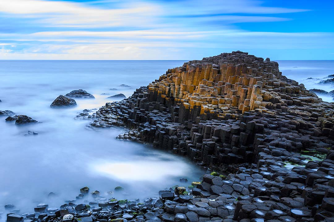 Giants Causeway jutting out into the sea that is covered in a fine layer of mist