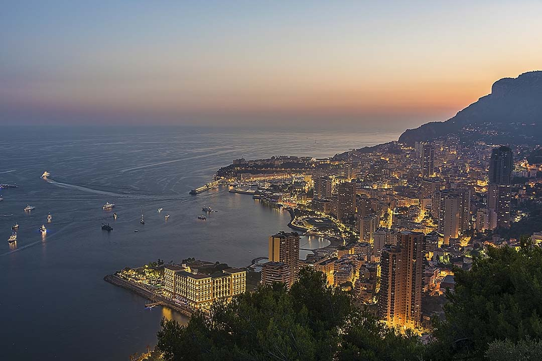 Towers and houses lit up at night in Monaco with the sun setting behind a hill.
