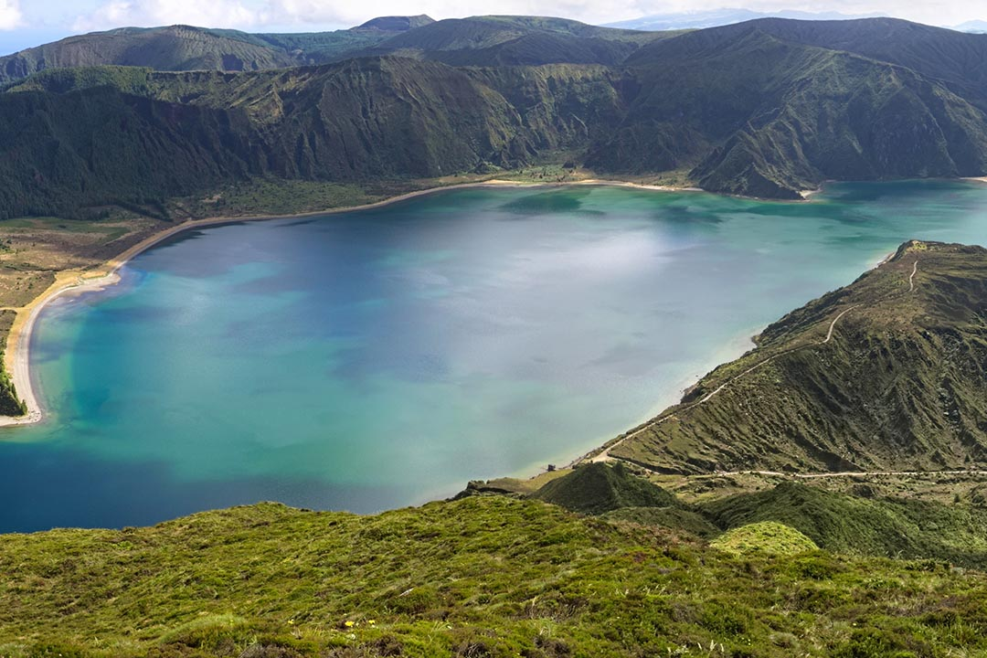 A volcanic crater lake, paths line the green ridges around the lake