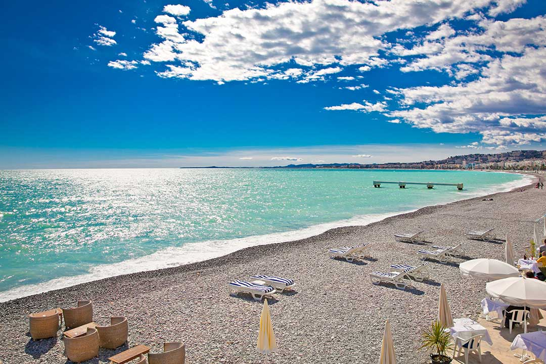 A pebble beach next to azure waters with sunloungers