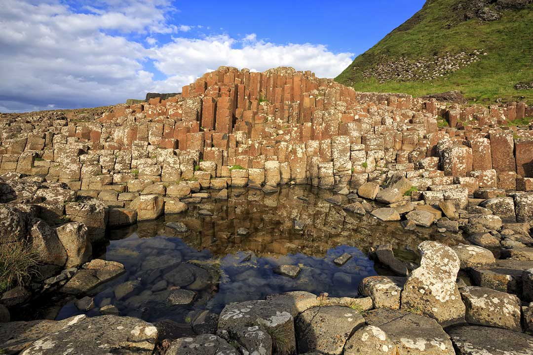 Cylindrical stones of Giant's Causeway with a clear rock pool