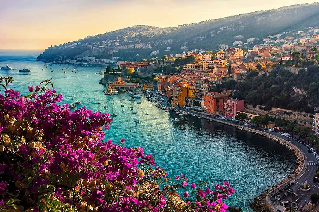 The French Riviera coast showing pastel coloured houses next to a beautiful blue sea