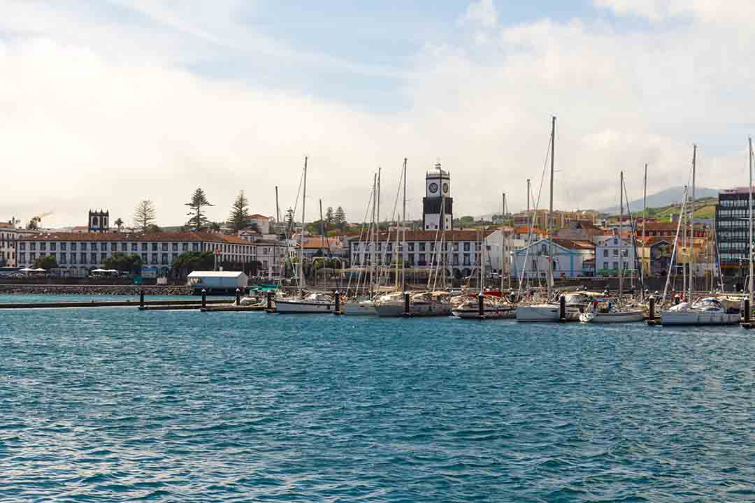 The harbour of Ponta Delgada, sail boats are moored in front of white buildings and a tall narrow church spire