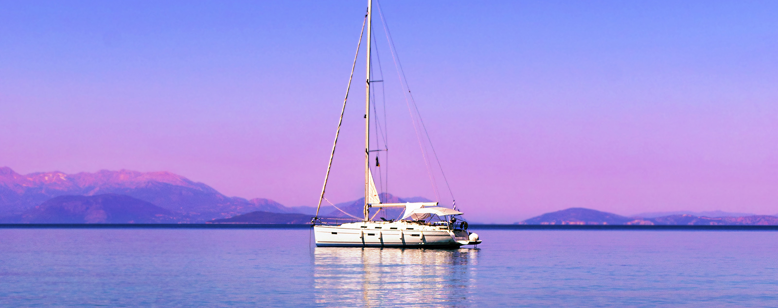 White yatch on the water with a light purple hue to the background