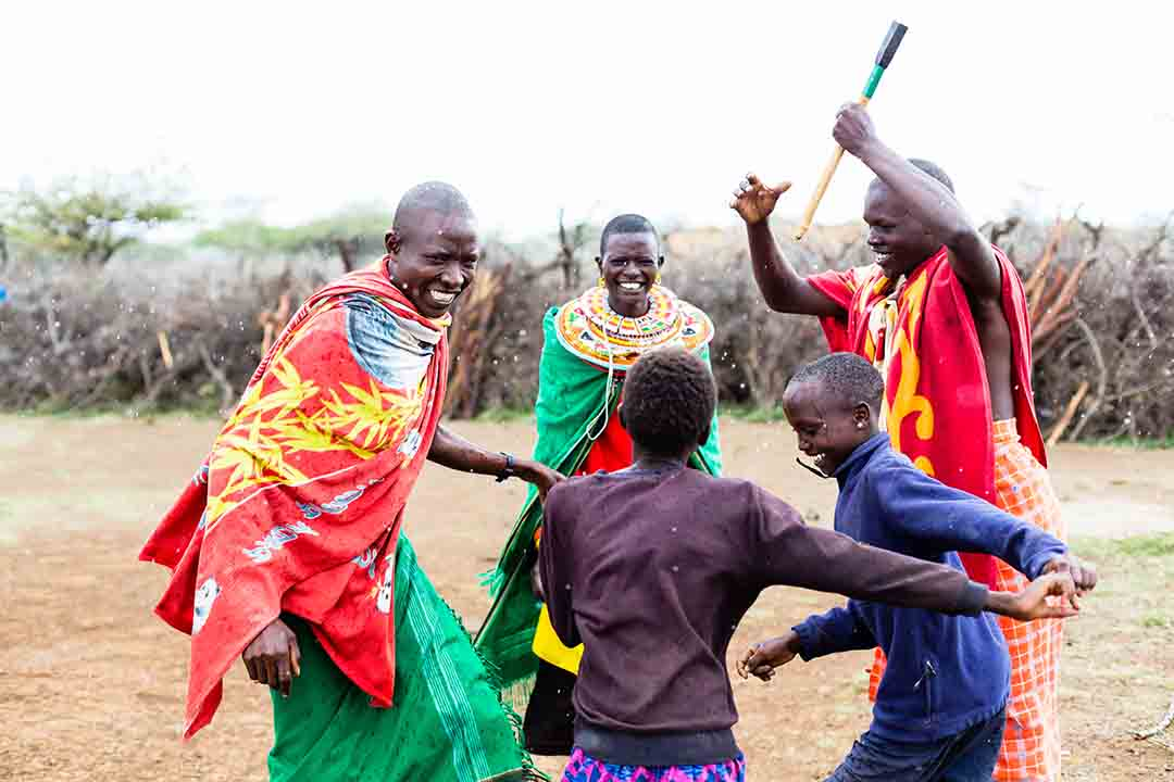 Masai family celebrating and dancing in colourful dress