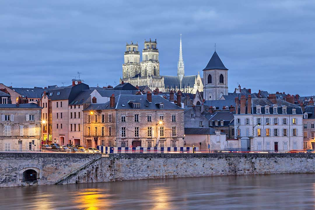 Enbankment on the river with large, old houses infront of a cathedral with a spire
