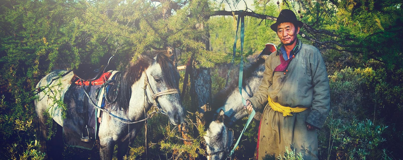 A traditionally dressed Mongolian man with his two horses surrounded by green trees