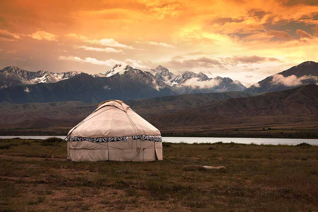 A traditional yurt surrounded by grassland and in the background towering snow topped mountains