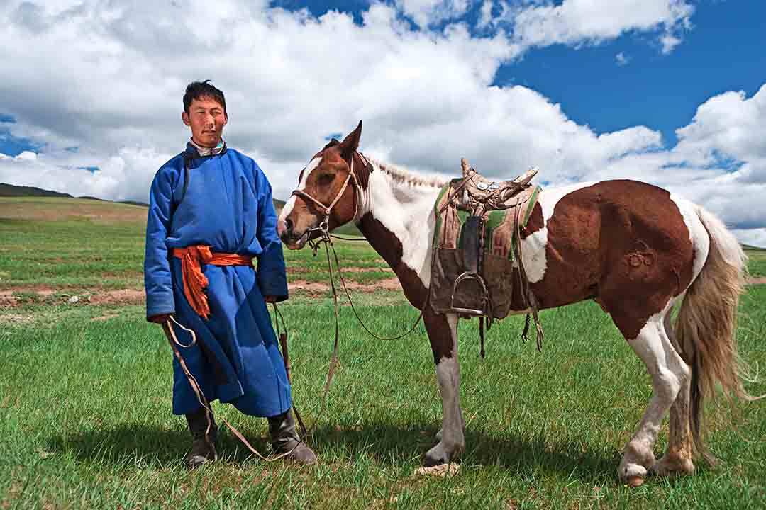 Mongolian horseback rider in traditional blue dress stands next to his brown and white horse