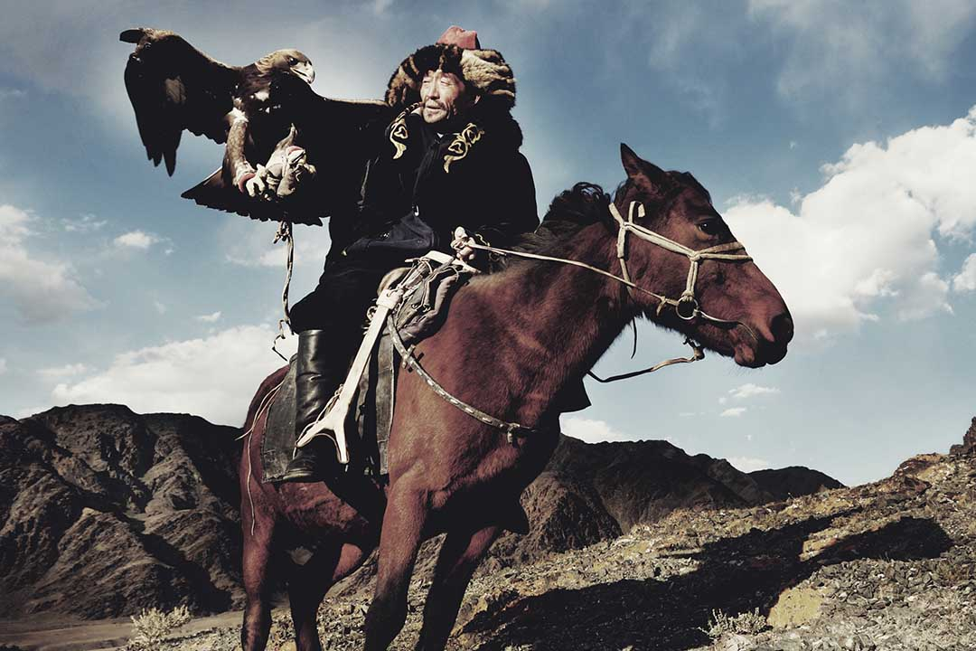 A Mongolian in traditional dress is riding a horse and a huge eagle is perched on his arm, rocky outcrops are in the background