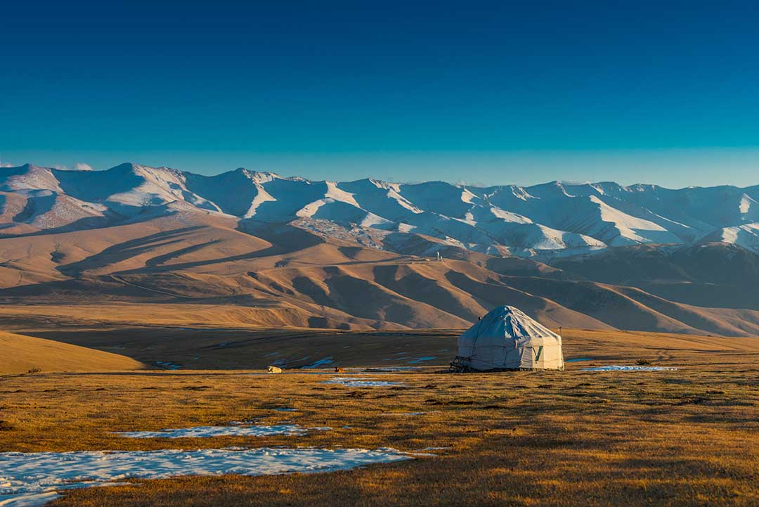 An isolated typical yurt surrounded by rolling hills leading to mountains in the background