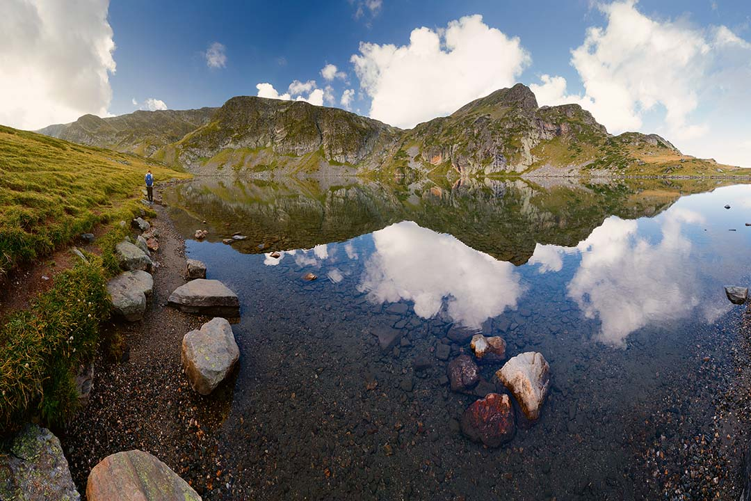 Mountainous grass covered hills are reflected in the perfectly clear water of a lake