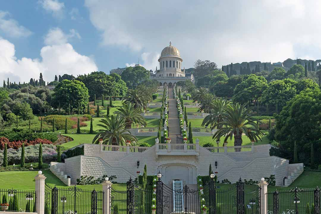 Ornate and gated gardens lined with bushes and palm trees ascend up to a domed temple