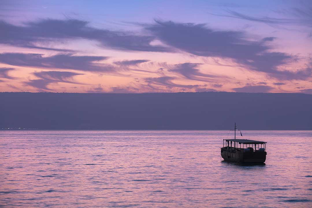 Beautiful Sea of Galilee in the morning. A narrow boat is cruising just before sunrise.