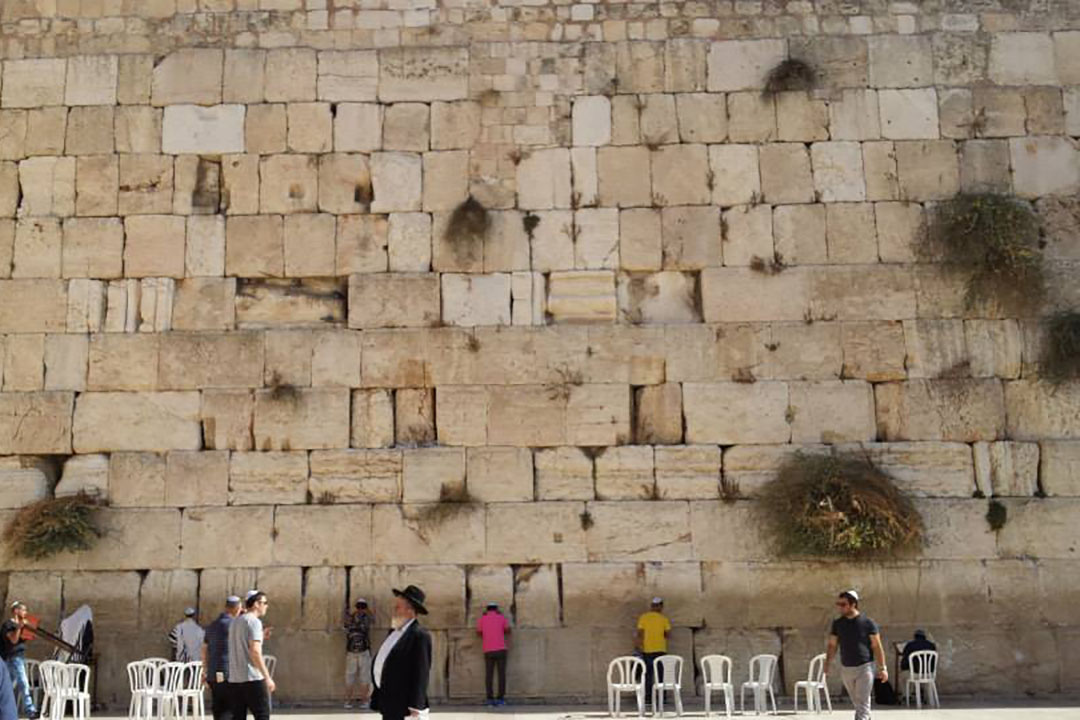 People pray facing the towering Western Wall. People can be seen placing written prayers between the cracks