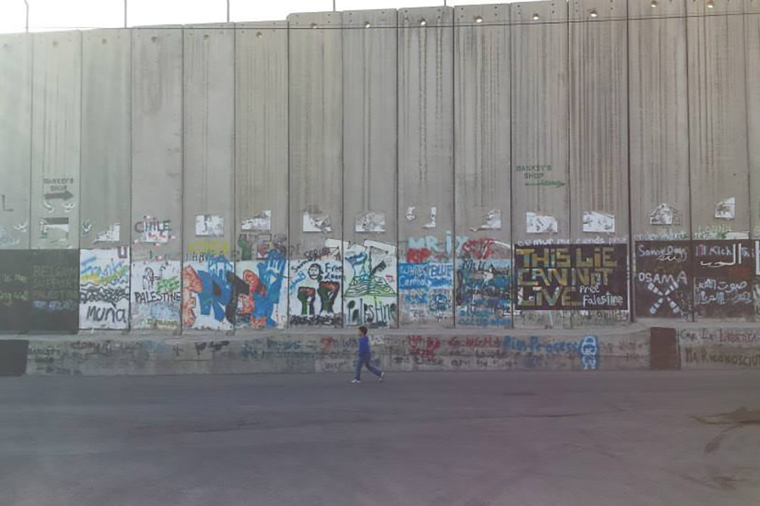 Graffiti and street art on a tall wall. A young boy walks alone in front of the wall