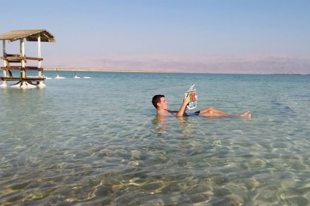 A man floats in the Dead Sea while reading a newspaper