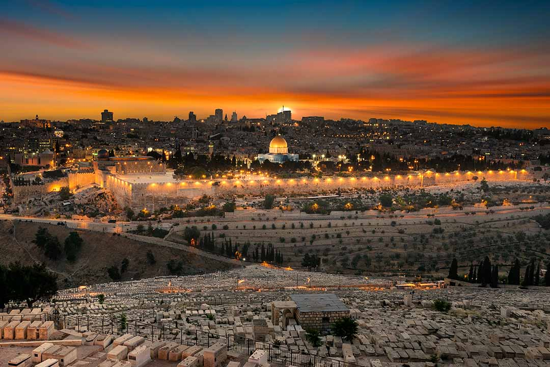 A red sunset illuminates the Jerusalem skyline looking back from the Mount of Olives