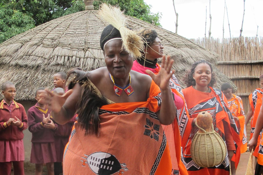A Swazi Chieften Woman dances and sings in an orange robe which has the Swazi emblem on it