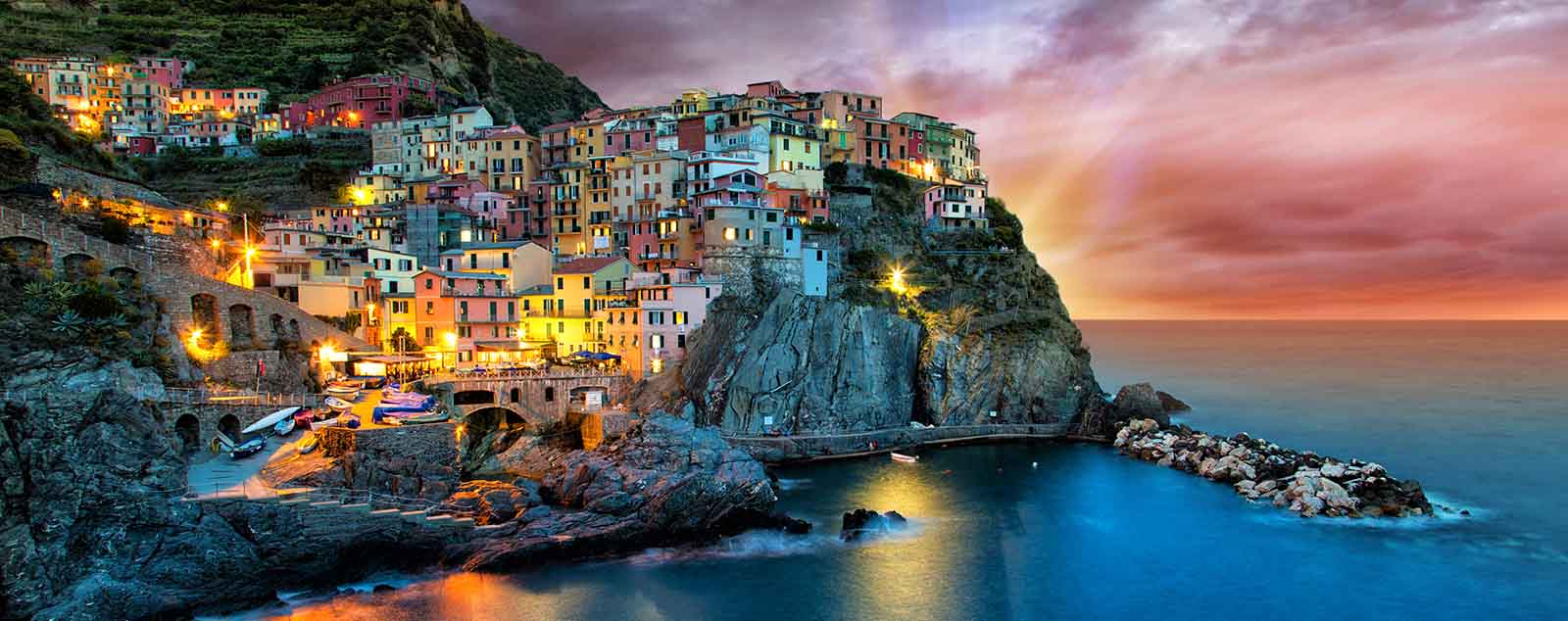 Pastel coloured houses clinging to jagged rocky cliffs, illuminated in the dusk by street lights