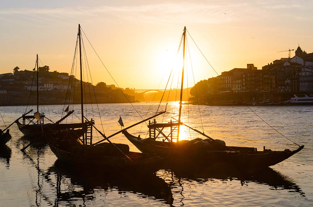 Sunset view over the bridges that cross the River Douro. The city is built on either bank and the long thin traditional fishing vessels are moored in the foreground