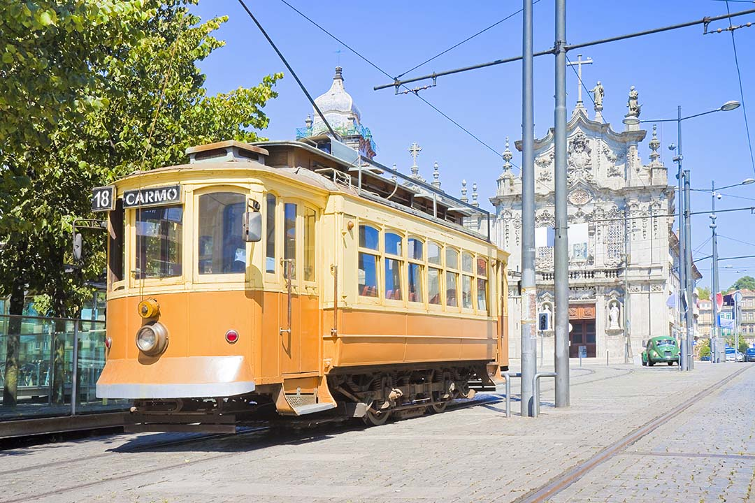 One of Porto's historic pastel coloured trams approaches an ornate church with green trees hanging overhead