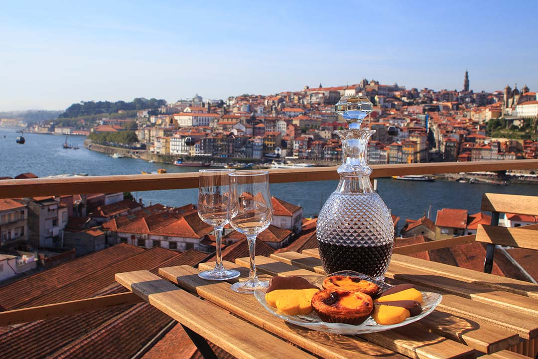 Table with view a wonderful view over the river Douro estuary in Porto, custard tarts and a decanter of port wine sit on the table
