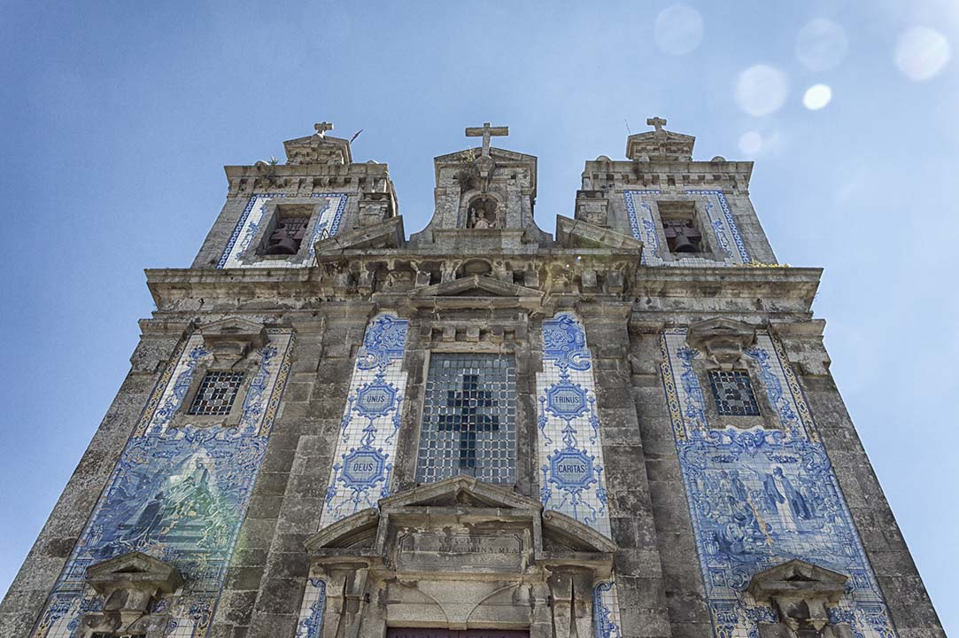 An eighteenth-century church facade, decorated with blue murals and many crucifix's