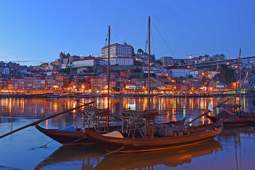 Long fishing vessels are docked, across the river estuary a sprawling town is a built on the river banks