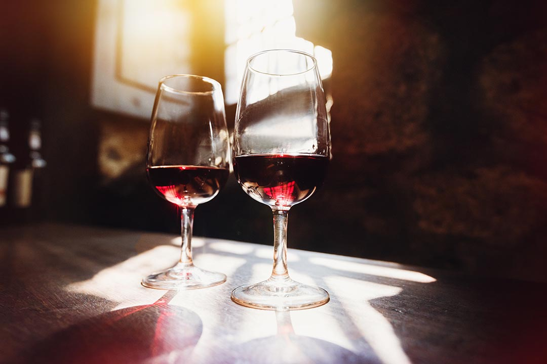 Two fine glasses of Port Wine on a wooden table with light streaming in from open shutters