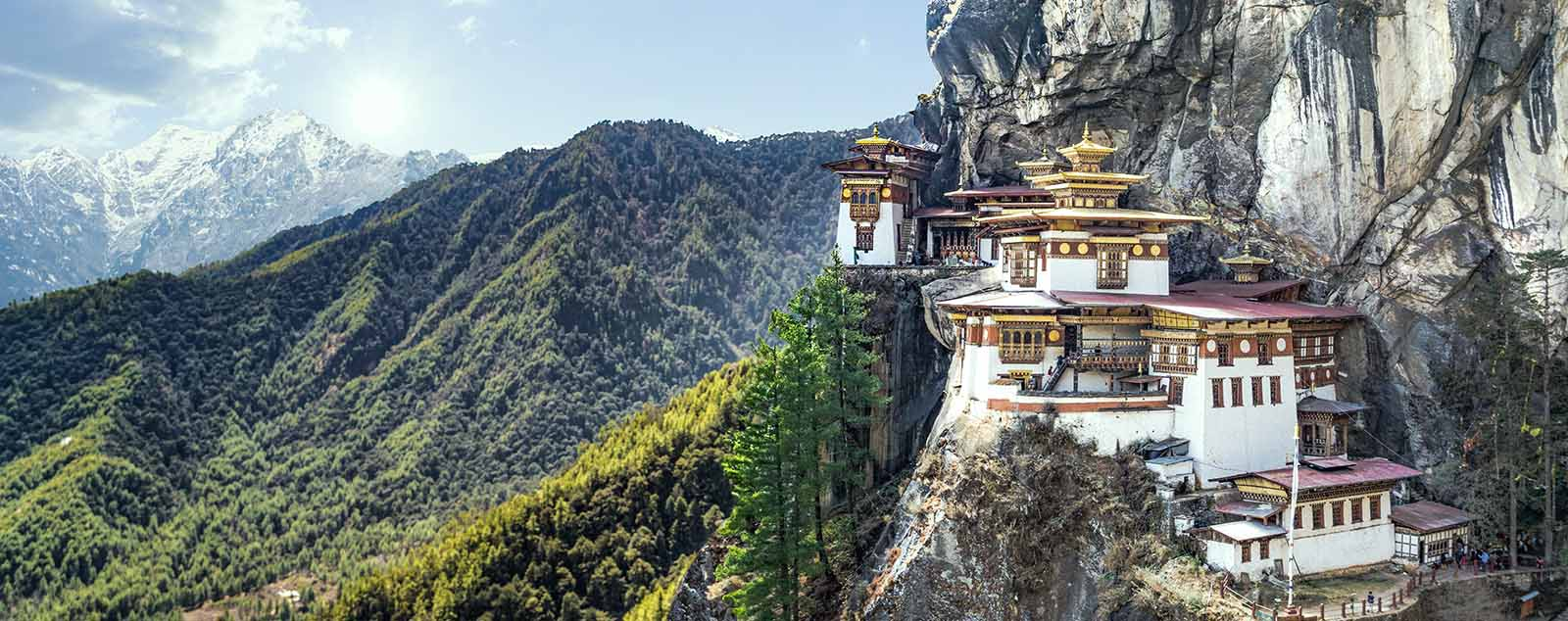 An ornate monastery built into the side of a steep cliff, tree covered and snow topped mountains stretch into the background