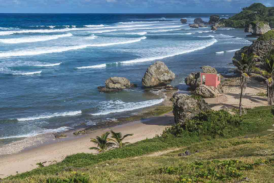 View over the beach at the town of Bathsheba, on the Atlantic east coast of Barbados. A derelict house can be seen on the beach surrounded by rocks cut into jagged shapes by the sea.