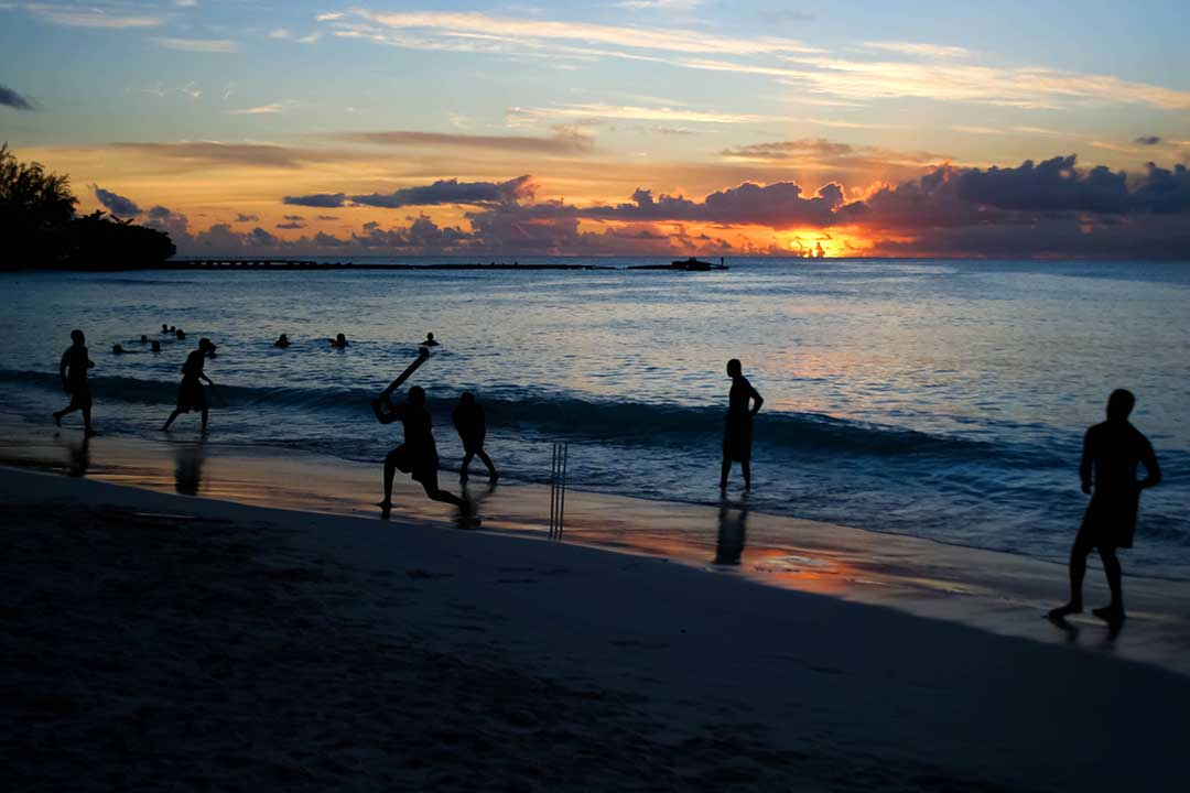 Bunch of friends playing cricket at the beach in Barbados as the sun sets behind the sea in the horizon.