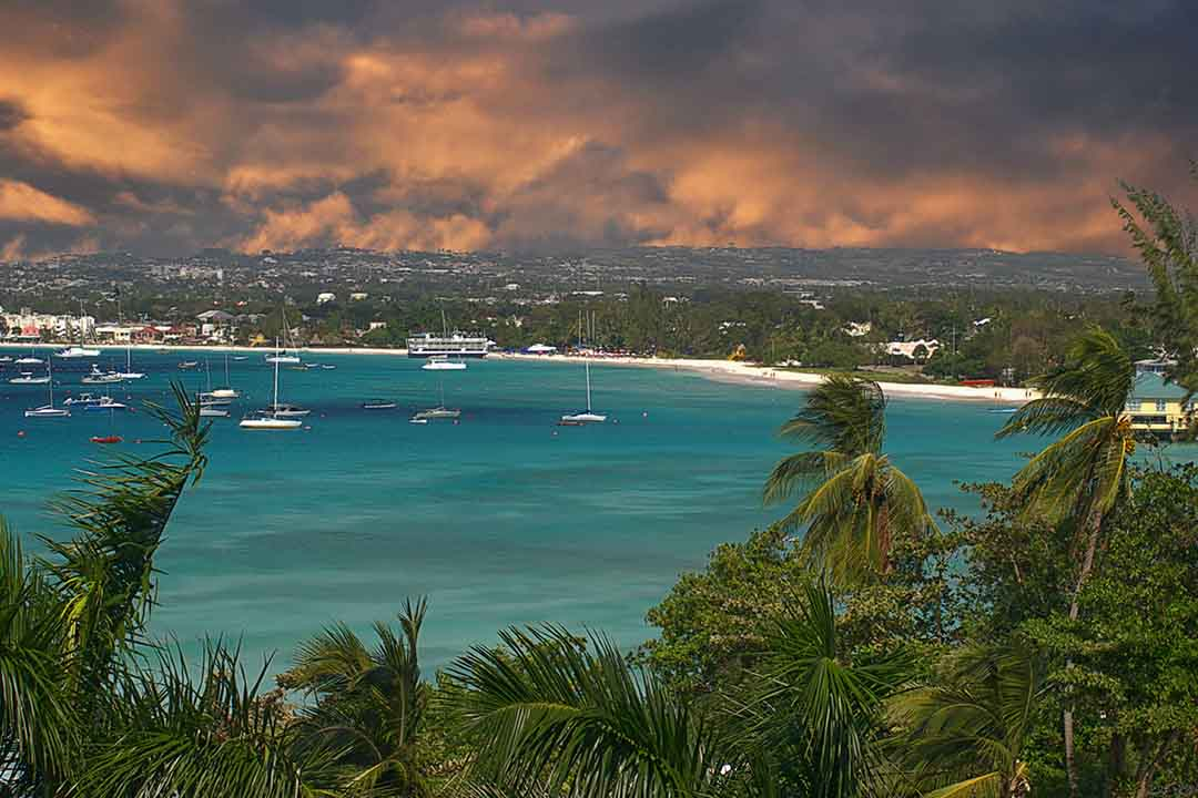 A red sky looms over swaying green trees and Barbados' coastline, with many yachts and boats moored in a sheltered bay.