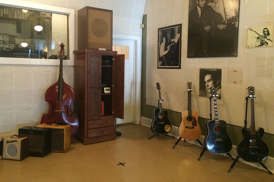 Numerous guitars on stands, posters, vinyl records and a cello