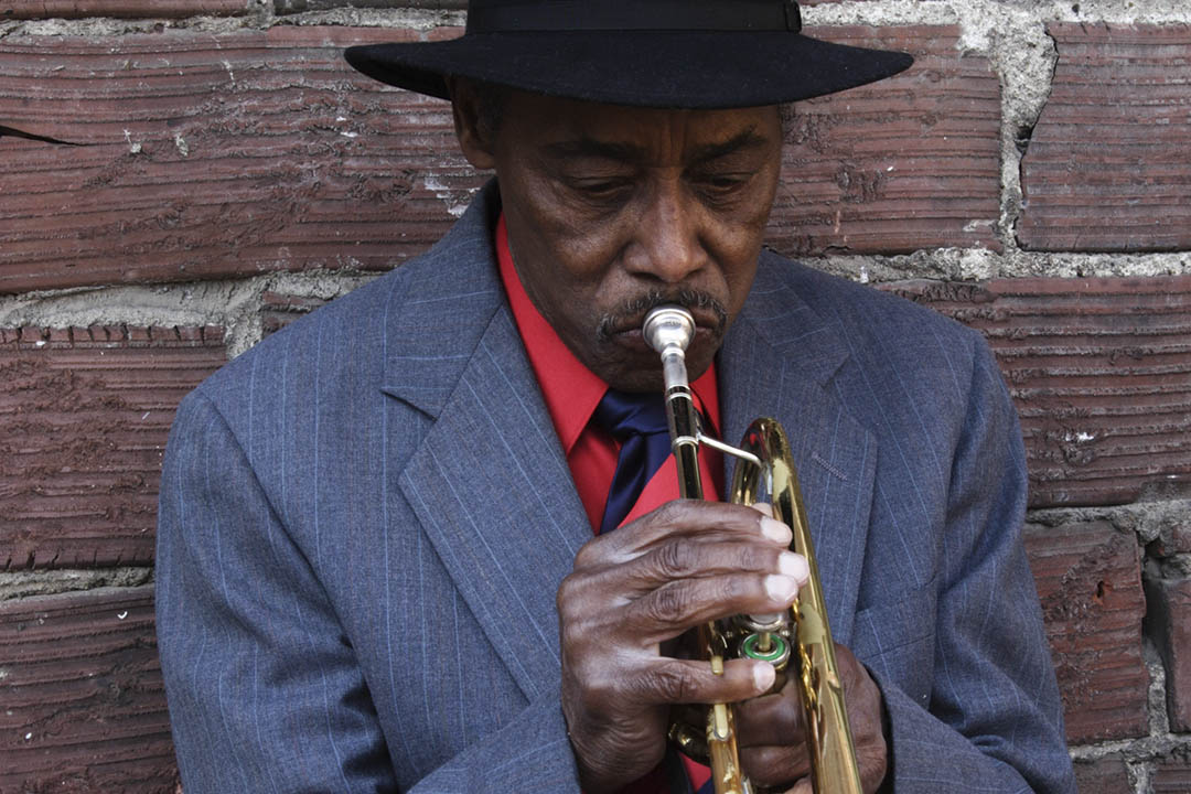 A suited gentlemen is playing the trumpet lent against a brick wall
