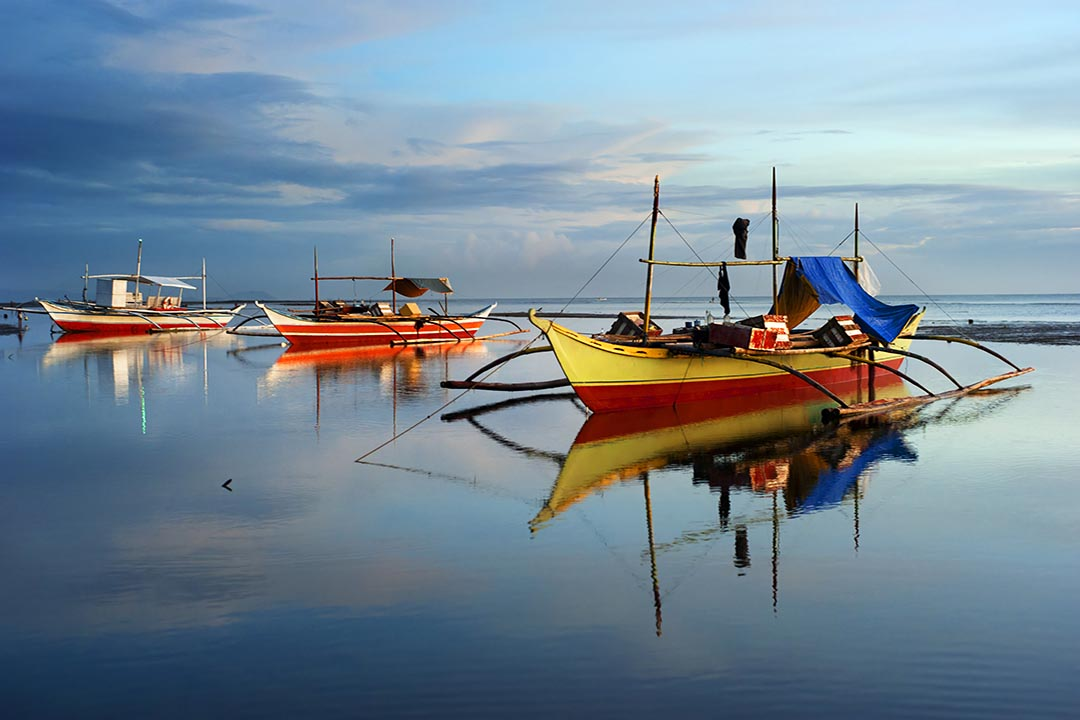 Traditional brightly coloured wooden fishing vessels on a tranquil sea